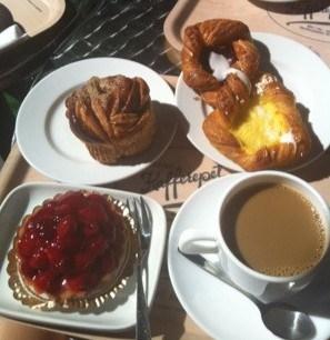 frukost bestående av en bakelse, kaffe, kardemummabulle och wienerbröd!