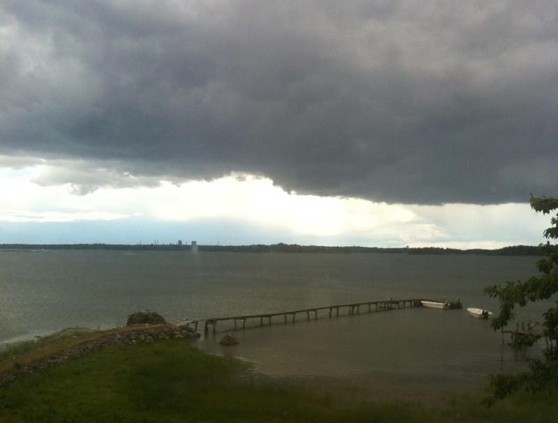 Utsikt vid hav och brygga på lantstället, mörka moln. Spara bilder på en molntjänst.