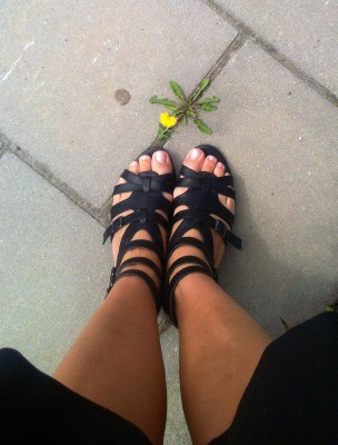 Arga Klara, fötter och en blomma som växer på stenplattor