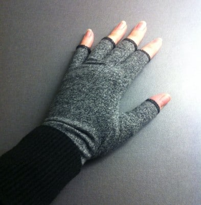 Hand med kompressionsvantar mot artrit.