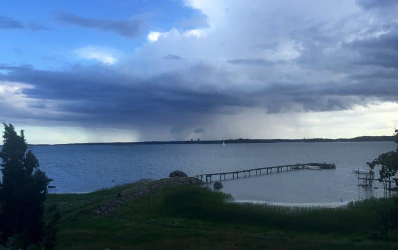 Vy från lantstället över hav och brygga, regn