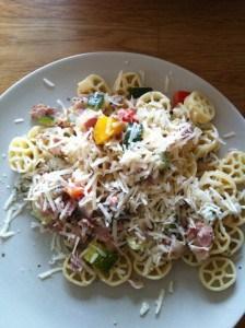 en tallrik med pasta, bacon och parmesanost