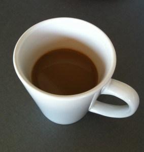 Kaffe i en vit kopp. Smärta på behandling, så vi fikade hemma.
