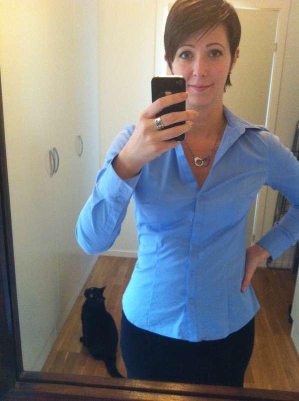 Arga Klara i blå skjorta med en besatt katt.