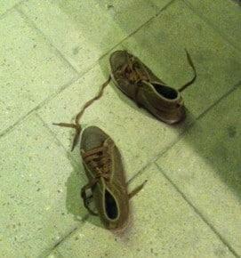 bruna skor övergivna på trottoaren