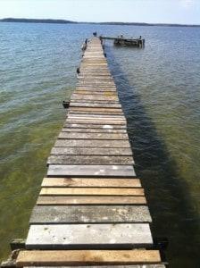 lång ranglig brygga i långgrunt vatten