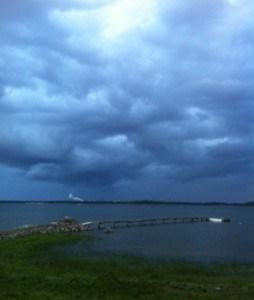 Regntunga skyar på lantstället. Svarta moln och mörk sjö, med utsikt mot järnverket i Oxelösund.