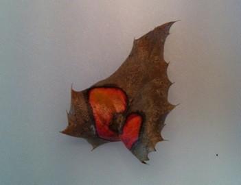 Ett torkat löv med orange färg i mönster som eldslågor