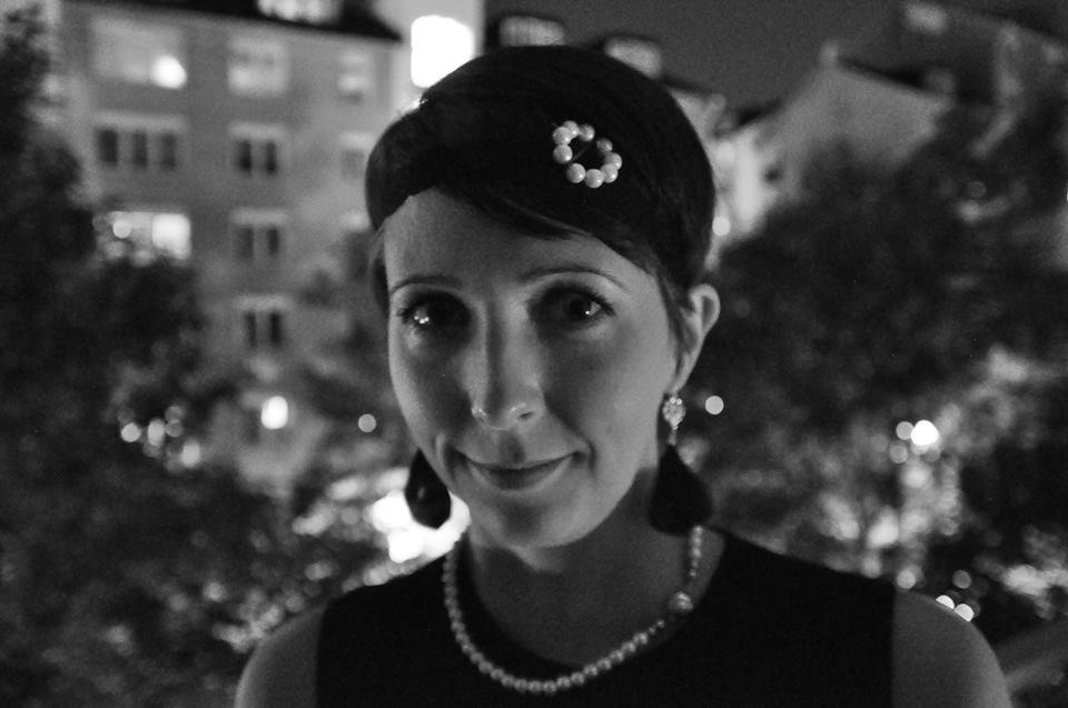 Om hår och nackspärr. Arga Klara i 20-talsfrisyr med pärlor och hårband.
