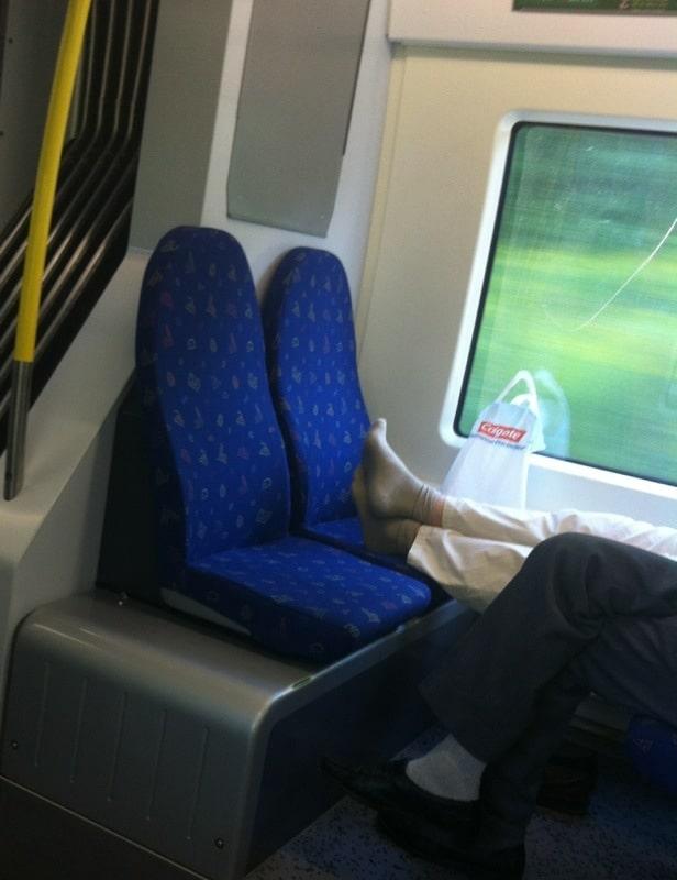 Vuxen man med fötter på sätet på pendeltåget. Idiot.