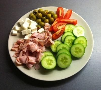 Mat, en tallrik med gurka, tomat, fetaost, skinka och oliver. God mat är lycka, är jag ensam ska det vara enkelt.