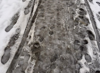 Slask på trottoaren efter snöfall.