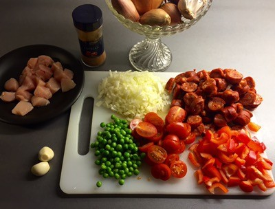 Ingredienser till paella; chorizo, kyckling, paprika, lök, vitlök, tomater, ärtor. Nyslipade knivar.
