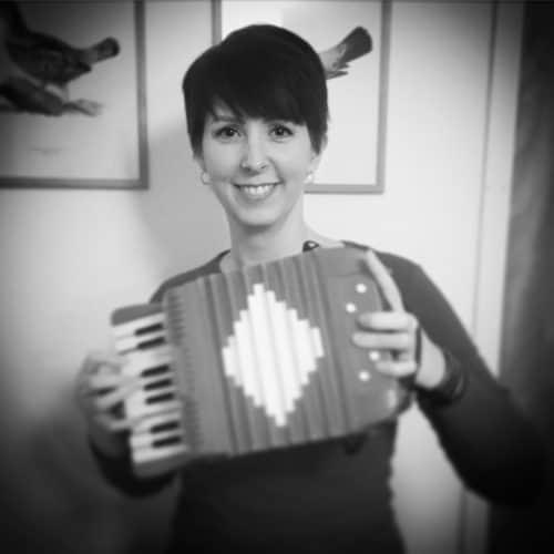 Arga Klara spelar dragspel, ett leksaksinstrument.