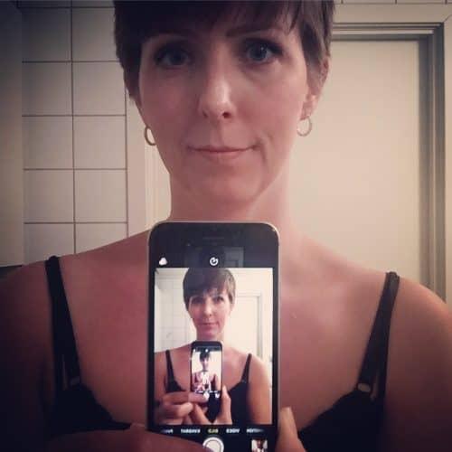Arga Klara i mobiltelefon i spegel. Har köpt ny telefon.